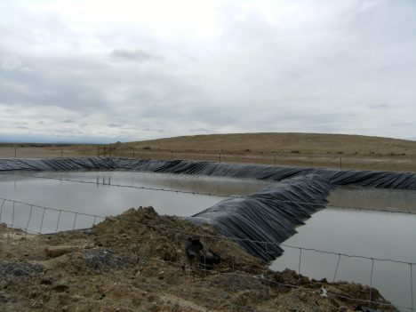 Open smelly pit with toxic hydrocarbon and chemical waste